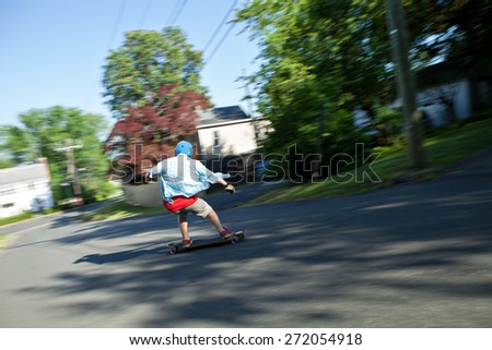 Longboarder skating on an urban road. Slight motion blur from panning technique to capture movement. - stock photo