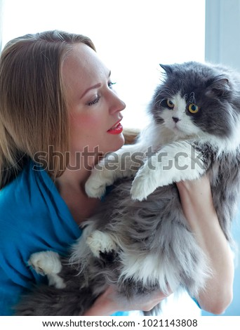 Longhaired blonde girl and grey cat relaxing on the window. Crossbreed cat