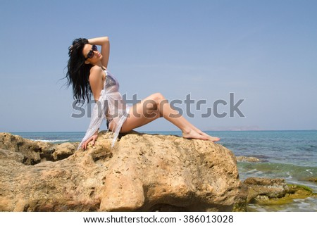 Longhaired brunette in black bikini enjoys summer at the beach.