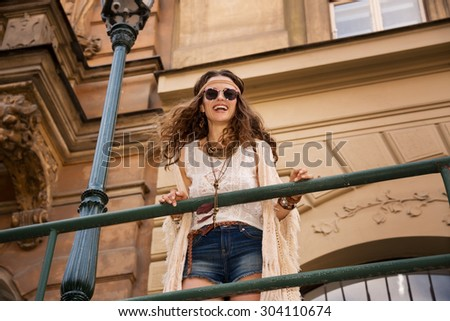 Longhaired hippy-lookin young lady in jeans shorts, knitted shawl and white blouse with sunglasses stands near streetlight in old town looking down and smiling - stock photo