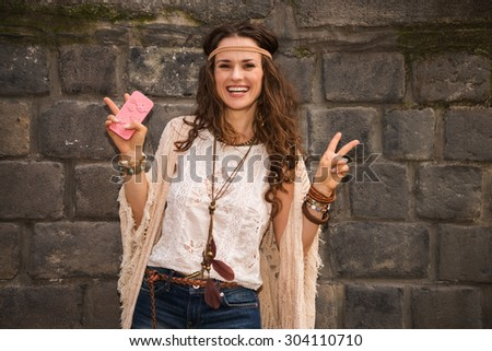 Longhaired hippy-looking young lady in jeans shorts, knitted shawl and white blouse standing near stone wall and showing victory gesture - stock photo