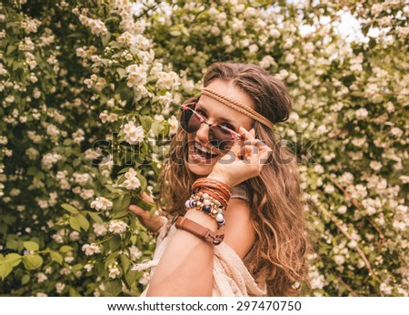 Longhaired hippy-looking young lady in knitted shawl and white blouse standing among flowers - stock photo