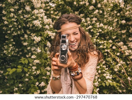 Longhaired hippy-looking young lady in knitted shawl and white blouse standing among flowers playing with retro camera - stock photo