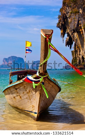 longtail boat is on the backdrop of scenic rocks in tropical sea
