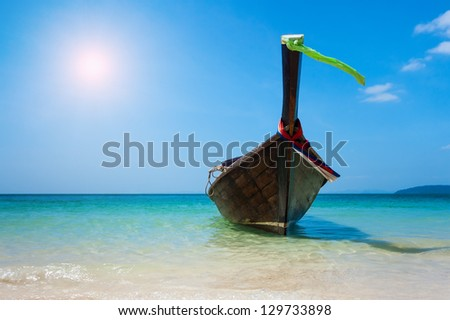 Longtail boat on the beach - stock photo