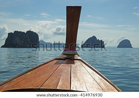 longtail boat prow in Thailand in the Andaman Sea with islands off the bow - stock photo
