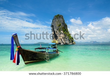Longtail boat with Poda island background at Krabi. Poda is famous island travel package tour by traditional longtail boat at Krabi, Andaman ocean Thailand - stock photo
