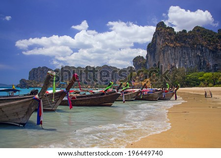 Longtail boats landing at Railay bay, Thailand. Picturesque rocks on the background - stock photo