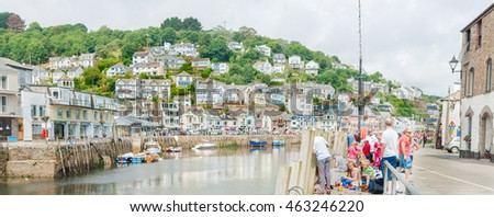 LOOE ENGLAND- JULY 23; : People gather and fish on Buller Street by East Looe River in the Cornwall coastal town of with homes covering the hill on opposite side jULY 23, 2013 Looe Engalnd.