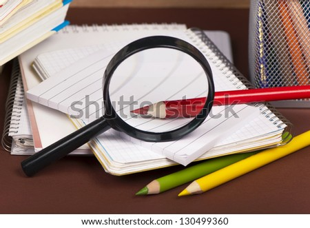 look at a red sharp pencil through magnifying glass - stock photo