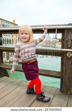 Look at me, I'm such a big girl now, I can hold on to the rail all by myself on this big bridge over the water... - stock photo