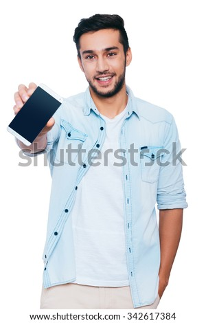 Look at my new smart phone! Handsome young Indian man showing his smart phone and smiling while standing against white background - stock photo