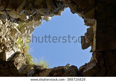 Look at the blue sky through the hole in the cave - stock photo