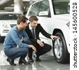 Look at these tires! Young car salesman showing the advantages of the car to the customer - stock photo