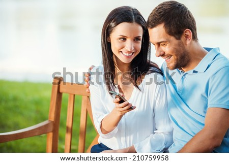 Look at this picture! Beautiful young loving couple sitting on the bench while woman showing mobile phone to her boyfriend and smiling - stock photo