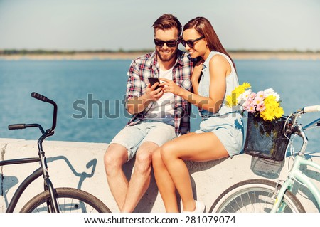 Look at this picture! Smiling young couple looking at mobile phone while sitting outdoors near their bicycles  - stock photo