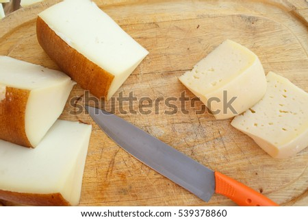 Look from above at knife with orange handle lying on board with cheese