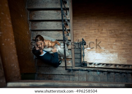 Look from above at wedding couple kissing on the stairs in dark corridor