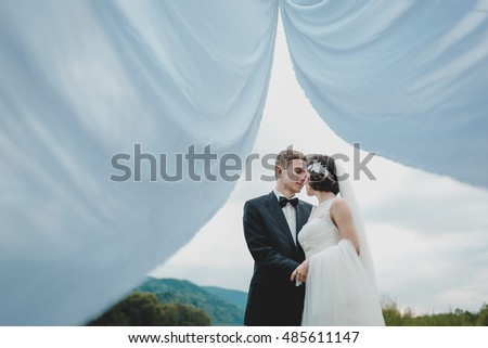 Look from between the white curtains at wedding couple hugging in the mountains