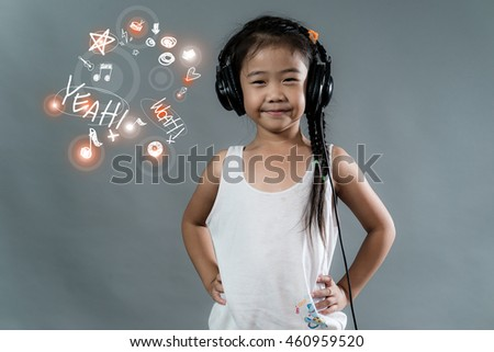 Look Good, Feel great! Relaxed Asian little girl listening to the music with headphones on grey background