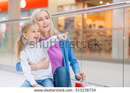 Look here. Pleasant happy mother standing with her daughter and pointing aside while having shopping together - stock photo