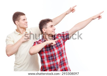 Look here. Two young handsome men standing on white isolated background and pointing with index fingers upwards.