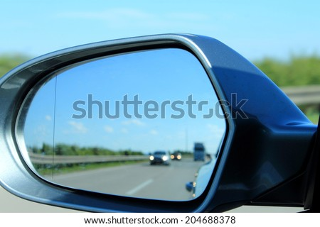Look in the side mirror on the car - stock photo