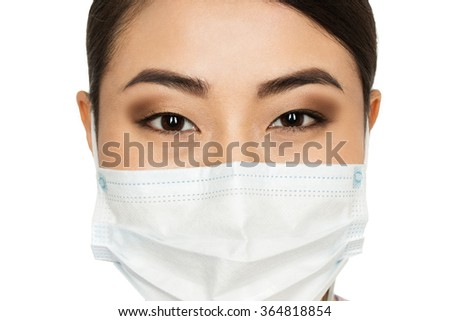 Look of confidence. Cropped closeup of an Asian female doctor wearing surgical mask against white background - stock photo