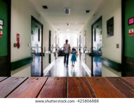 Look out from the table, blur image of a mother and daughter walking on the dark corridor in the hospital as background. - stock photo
