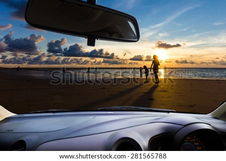 Look out the car window to see the sunset on the beach for use as a background. - stock photo