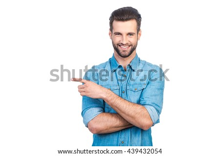 Look over there! Happy young handsome man in jeans shirt pointing away and smiling while standing against white background  - stock photo