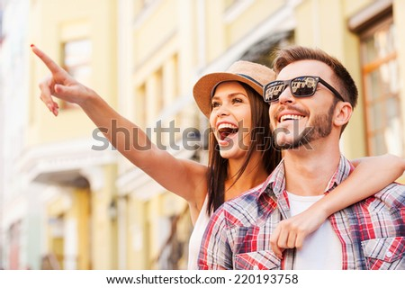Look over there! Happy young loving couple bonding to each other while beautiful woman pointing away and smiling  - stock photo