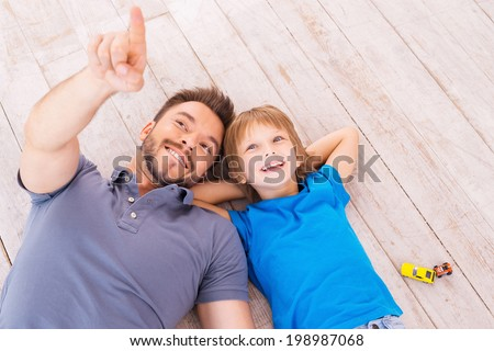 Look over there! Top view of happy father and son lying on the hardwood floor together while young man pointing away and smiling