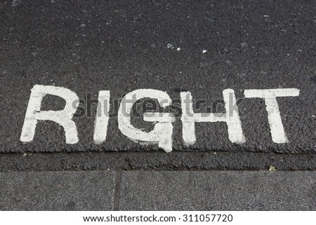Look right before crossing, sign on the asphalt road - stock photo
