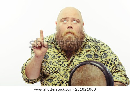 Look there. Portrait of funny bearded man holding African drums and pointing up with a serious face expression while standing isolated over white background