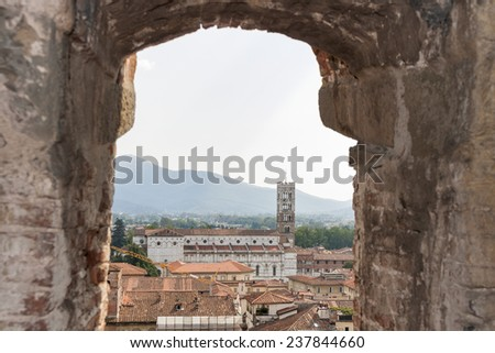 Look through a window over the Cathedral of San Martino of Lucca in Tuscany, Italy, from inside the the Guinigi tower - stock photo