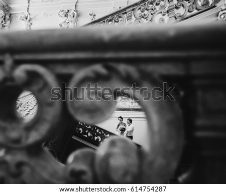 Look through the handrails at groom touching bride tender on the stairs