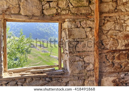 Look through window from abandoned stone house in the mountain - stock photo