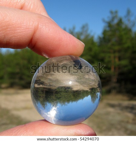 Look to inverted world through the crystal ball in fingers - stock photo