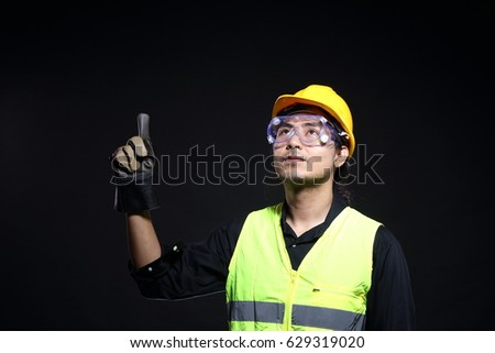 Look up and point fingers hands up of Architect Engineer in hard hat,  safety vest equipment, thick gloves and protector glasses goggle, studio lighting black background copy space