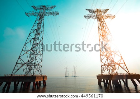 Look up at High-voltage power transmission towers in the sea skyline
