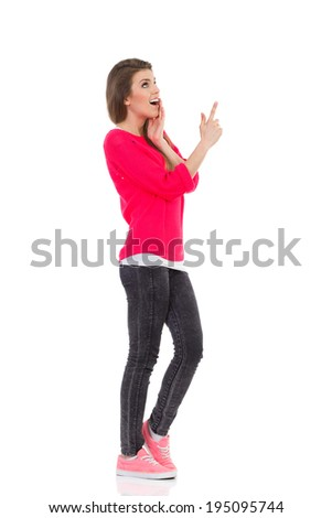 Look up there! Surprised young woman pointing up at empty space. Full length studio shot isolated on white. - stock photo
