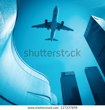 look up to the airplane and see modern buildings skyline - stock photo