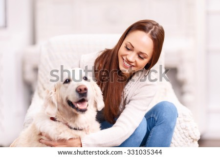Look who is back. Attractive young lady is grinning broadly while patting and caressing her cute pet dog.