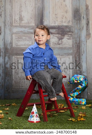 Look who's two!  Adorable toddler sitting on a red ladder with a party hat on the ground and a number two in the background. - stock photo