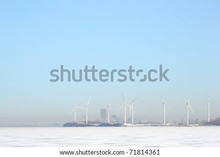 Looking across a frozen Lake Erie in winter at a group of windmills along the Lake Erie shoreline near a misty  Buffalo New York. - stock photo