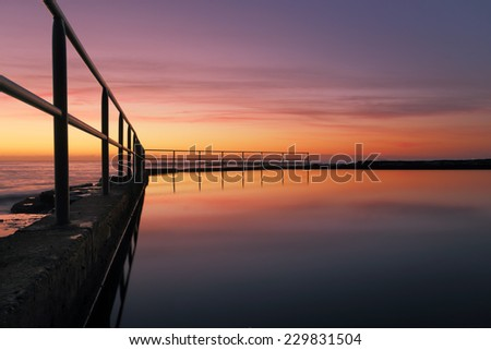 Looking across the ocean rock pool at Wombarra NSW Australia with a beautiful sunrise sky reflected in the pools water. - stock photo