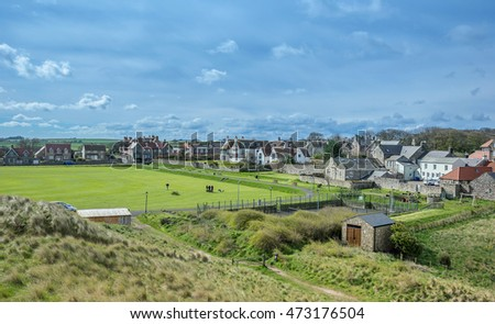 Looking across the playing field to the rooftops of Bamburgh on the north east coast of Northumberland in England