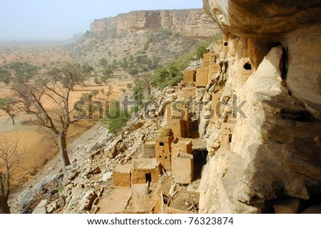 Looking along and down from the Bandiagara cliff to Dogon and Tellem buildings and surrounds - stock photo