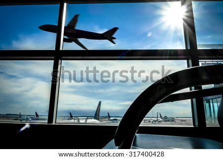 Looking at a airplane taking off from the inside of a lounge in the airport - stock photo